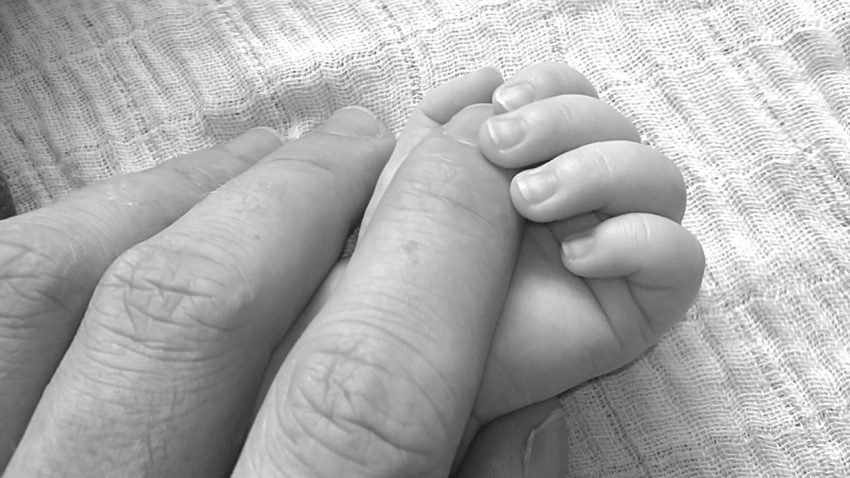 baby holding moms hand